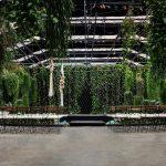 Podium in de vijver met groene achterwand trouwen in een kas